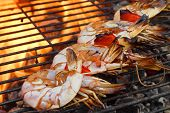 stock photo of bbq party  - Skewered Big Shrimps On The Hot BBQ Grill Flames of Fire In The Background - JPG