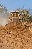 foto of bulldozer  - Large bulldozer moving rock and soil for fill for a new commercial development road construction project - JPG