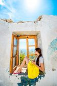 stock photo of abandoned house  - Young woman sitting on the window with sea view in abandoned house - JPG