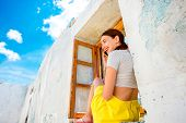 foto of abandoned house  - Young woman talking with phone sitting on the window in abandoned house - JPG