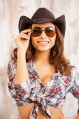 picture of cowgirls  - Beautiful young cowgirl adjusting her eyewear and smiling at camera while standing against the wooden background - JPG