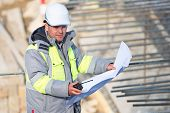 stock photo of inspection  - Civil Engineer at at construction site is inspecting ongoing production according to design drawings - JPG