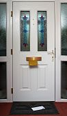 stock photo of front door  - The inside of a front door with a letter in the in flap and on the doormat - JPG