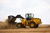image of wheel loader  - Front end loader clearing a construction site - JPG