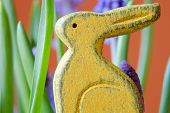 image of cony  - Yellow wooden bunny between green shoots of spring grass and blue flowers - JPG