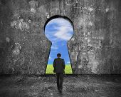 stock photo of keyholes  - Businessman walking toward keyhole door with natural sky clouds grass view on mottled concrete wall background - JPG