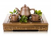 pic of loam  - still life of the clay teapot and cup on wooden trivet on white background isolated - JPG