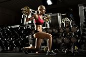 stock photo of execution  - beautiful girl bodybuilder execute exercise with dumbbells in dark gym - JPG