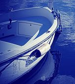 picture of outboard engine  - wooden boat by the shore in blue - JPG
