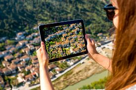 image of albania  - Young woman tourist photographing with tablet Berat city from the castle mountain in Albania - JPG