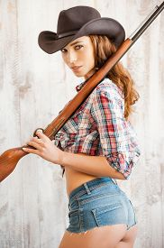 stock photo of cowgirl  - Beautiful young cowgirl carrying gun on her shoulders while standing against the wooden background - JPG