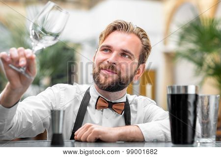 Barman checking the cleanliness of glass