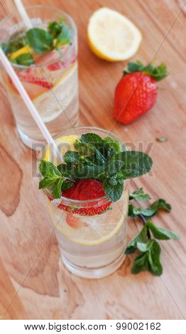 homemade lemonade with mint and strawberries on a wooden