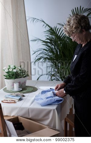 Senior Woman Packing Husband's Clothes