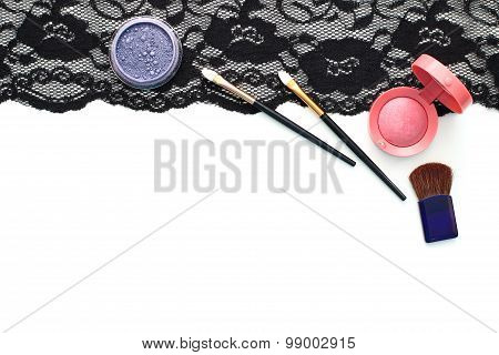 make-up brushes and cosmetics on black lace