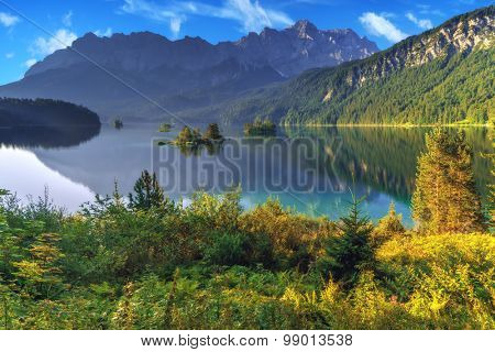 Fantastic sunny day on mountain lake Eibsee, located in the Bavaria, Germany. Dramatic unusual scene. Alps, Europe.