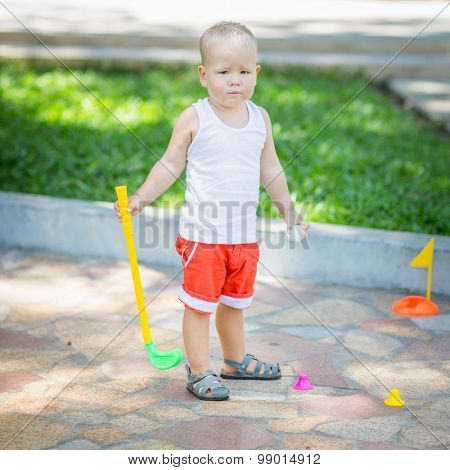 Baby boy playing toy golf outdoor
