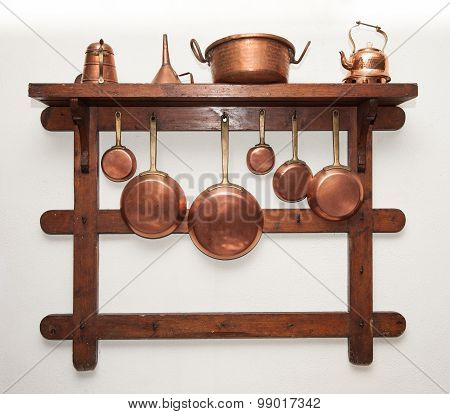 Vintage Copper Cookware Hung On Wooden Shelf