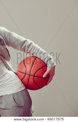 Sporty Teen Girl Holding Basketball With One Hand.