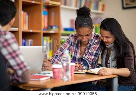 Couple of female students studying for exam after lecture in college