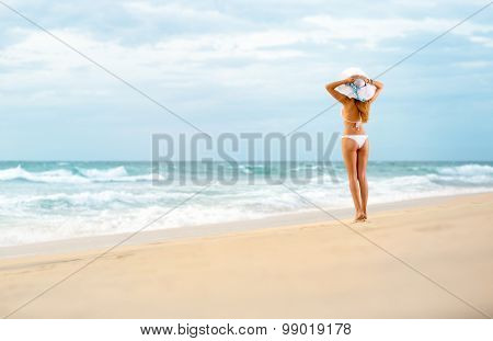 Attractive fit woman standing on  beach, summertime