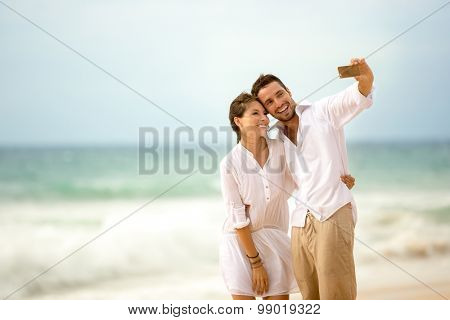 Happy romantic couple on the beach taking photo of themselves with smart phone