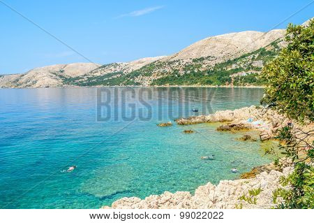 Beautiful Rocky Beach With Crystal Clear Sea And People Snorkeling