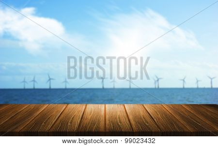 3D render of a wooden table looking out to a wind farm in the sea