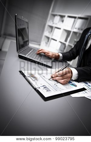 hands doing paperwork with pen and laptop.