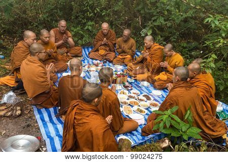 CHIANG DAO, THAILAND, JANUARY 06, 2015: Group of Buddhist monks praying for new year celebration before an outdoor lunch in the foggy wild nature of the Chiang Dao mount in Thailand.