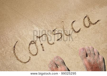 Conceptual Corsica text handwritten in sand for natural, symbol,tourism or conceptual designs background with feet
