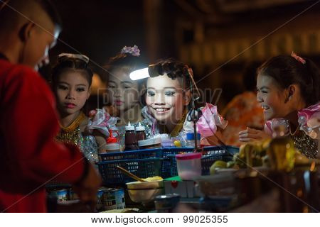 CHIANG MAI,THAILAND,JANUARY 04,2015: A Thai traditional dancer little girl is ordering a banana pancake to the street seller during the saturday night market in Chiang Mai,Thailand.