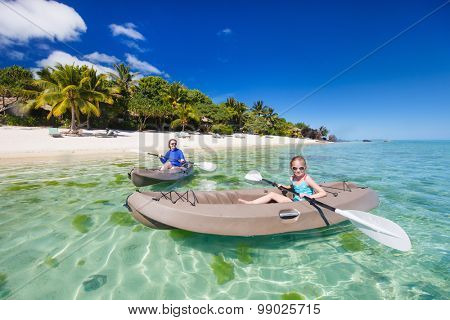 Family og mother and daughter paddling on kayaks at tropical ocean water during summer vacation