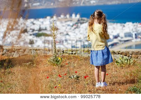 Back view of little girl enjoying views of traditional white village on Mykonos island, Greece