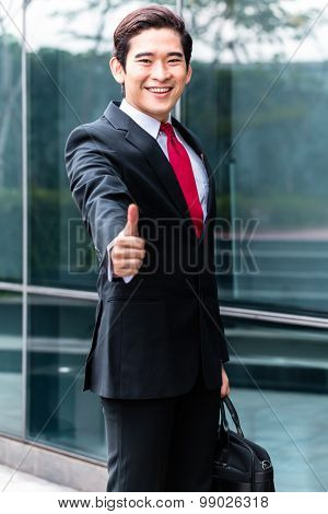 Asian businessman walking in front of building