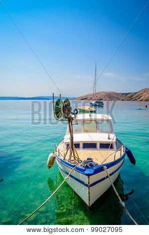 A Boat Tied On A Dock On The Crystal Clear Blue Sea