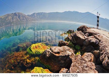 Stones beach with sea and mountain views. fisheye look. Montenegro