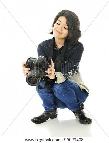 A pretty young teen squatting with her camera.  She appears mighty pleased as she looks at the image in the back.  On a white background.