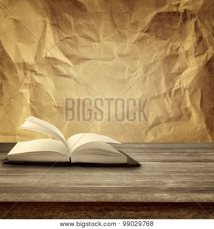 Open book on table in front of paper background