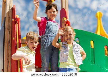 summer, childhood, leisure, friendship and people concept - group of happy kids waving hands on children playground