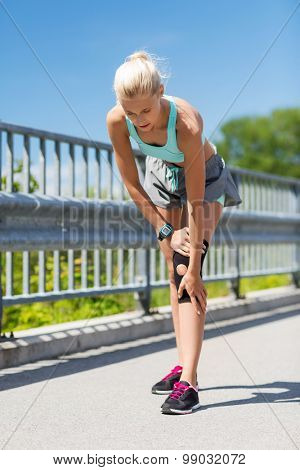 fitness, sport, exercising and healthy lifestyle concept - young woman with injured knee or leg outdoors