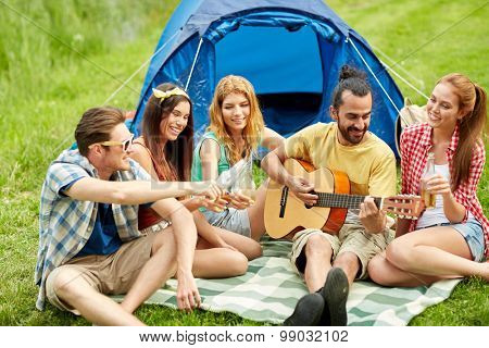 travel, tourism, hike, picnic and people concept - group of happy friends with tent and drinks playing guitar at camping