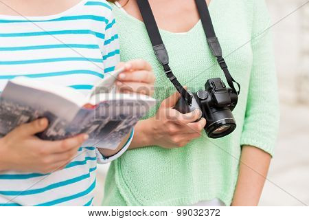 tourism, travel, leisure and friendship concept - close up of women with city guide and camera outdoors