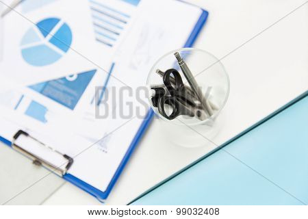 business, stationery and office supply concept - close up of organizer with scissors and pens over charts on table