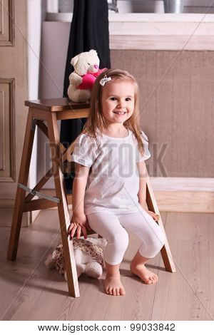 Little Cute Blond Girl Sitting On Small Wooden Ladder In Room With Soft Toys