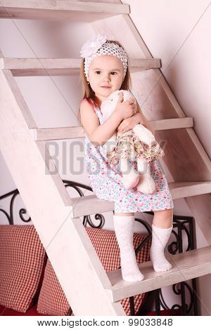 Little Cute Blond Girl In Dress Sitting On Wooden Stairs With Soft Toy In Her Hands