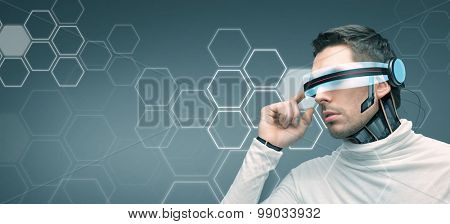 people, technology, future, network and progress - man with futuristic 3d glasses and microchip implant or sensors over blue background with hexagonal structure