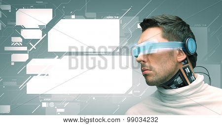 people, technology, future and progress - man with futuristic glasses and microchip implant or sensors over green background and blank virtual screens