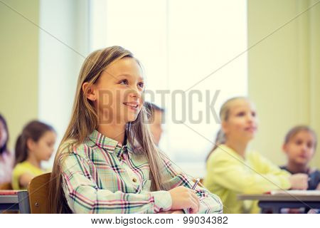 education, elementary school, learning and people concept - group of school kids with notebooks sitting in classroom