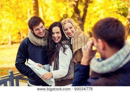 travel, people, tourism, photography and friendship concept - group of smiling friends with map taking picture in city park